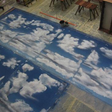 Der Blick in einen Malersaal von obern fotografiert. Bemalter Stoff liegt auf dem Boden, es sind weiße Wolken vor einem blauen Himmel zu sehen. Zwei Farbeimer und ein großen 2 Meter langes Lineal stehen daneben.